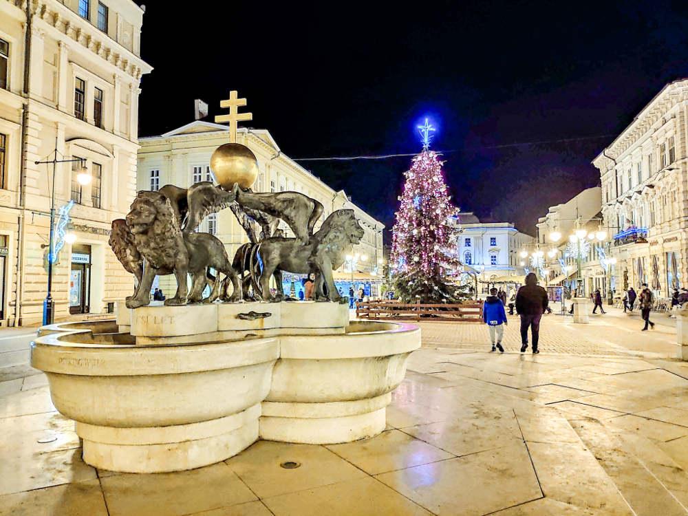 Milenijumska fontana u Segedinu u večernjim satima i velika okićena jelka božićnog marketa