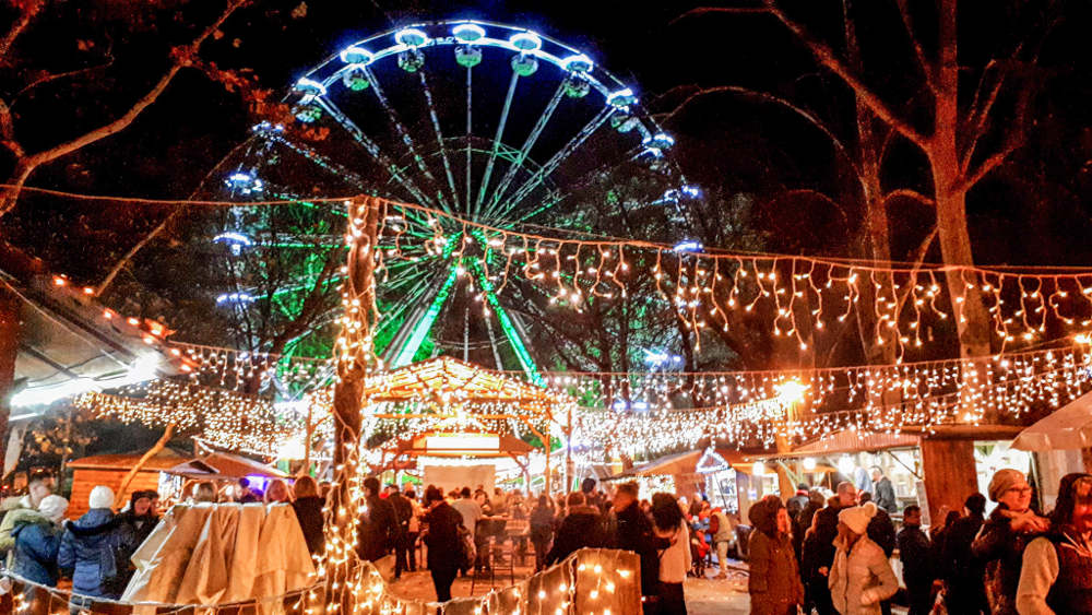 Svetla panoramskog točka i božićnog marketa u Segedinu u večernjim satima